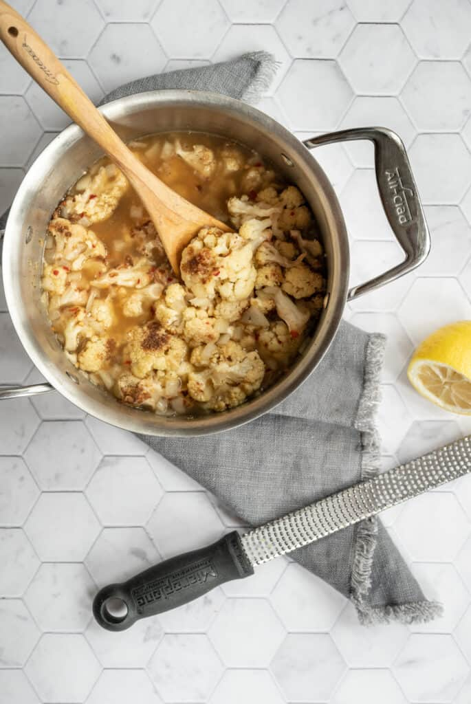 soup pot of roasted cauliflower and broth with a wooden spoon on a gray napkin and a lemon and zester on a marble hexagon tile background