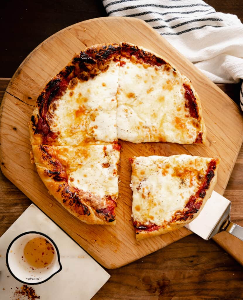 a pizza on a peel with one piece being served and a marble trivet with spicy honey in a bowl
