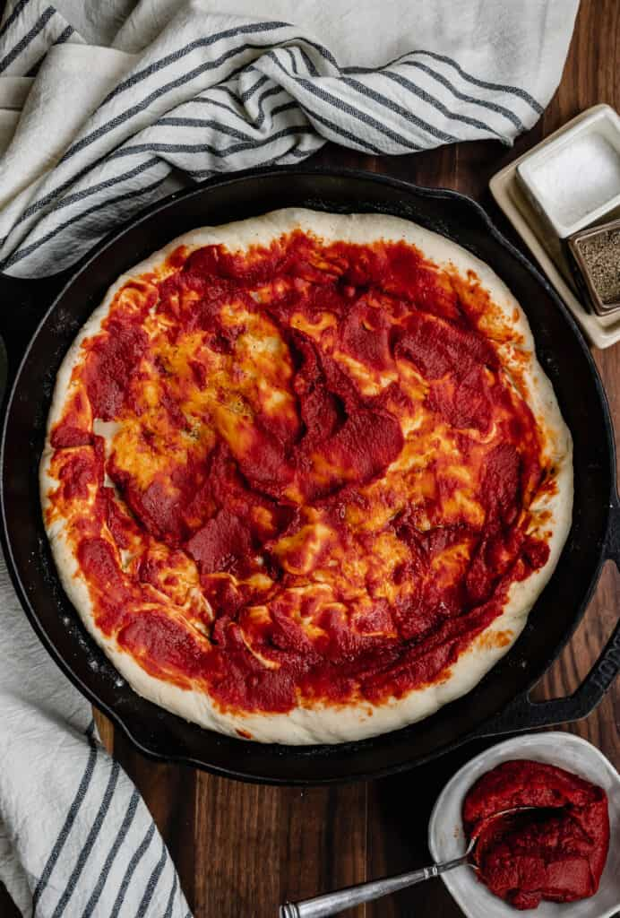 tomato sauce on pizza dough in a cast iron skillet with a black and white towel near a white bowl of tomato sauce next