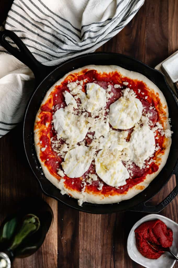 cast iron skillet pizza with soppressata, fresh mozzarella and parmesan on a walnut board with toppings and a black and white cloth