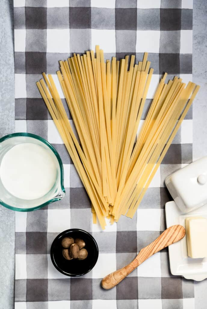 gray checked background with ingredients for fettucine with butter and cream and a bowl of whole nutmeg