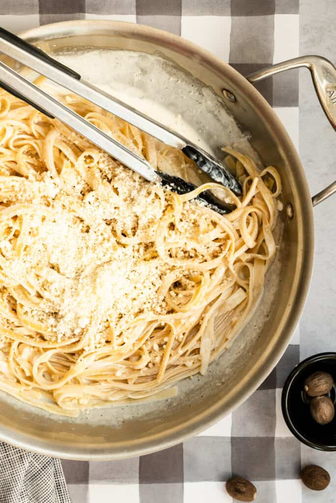 a stainless pan of fettuccine alfredo with some tongs on a gray checked backdrop and some whole nutmeg in a small black bowl