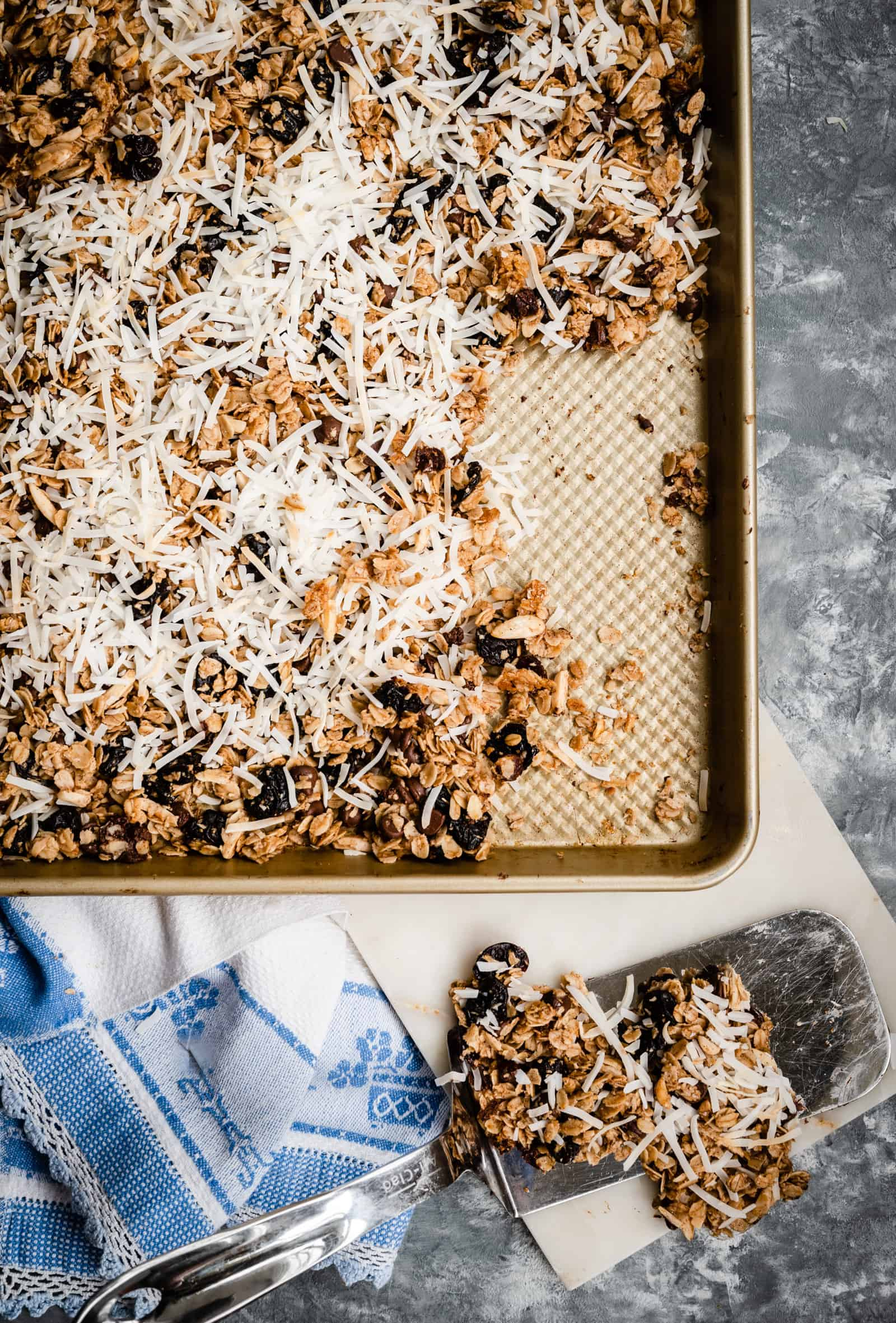 baking sheet of coconut covered baked granola and a spatula removing a section
