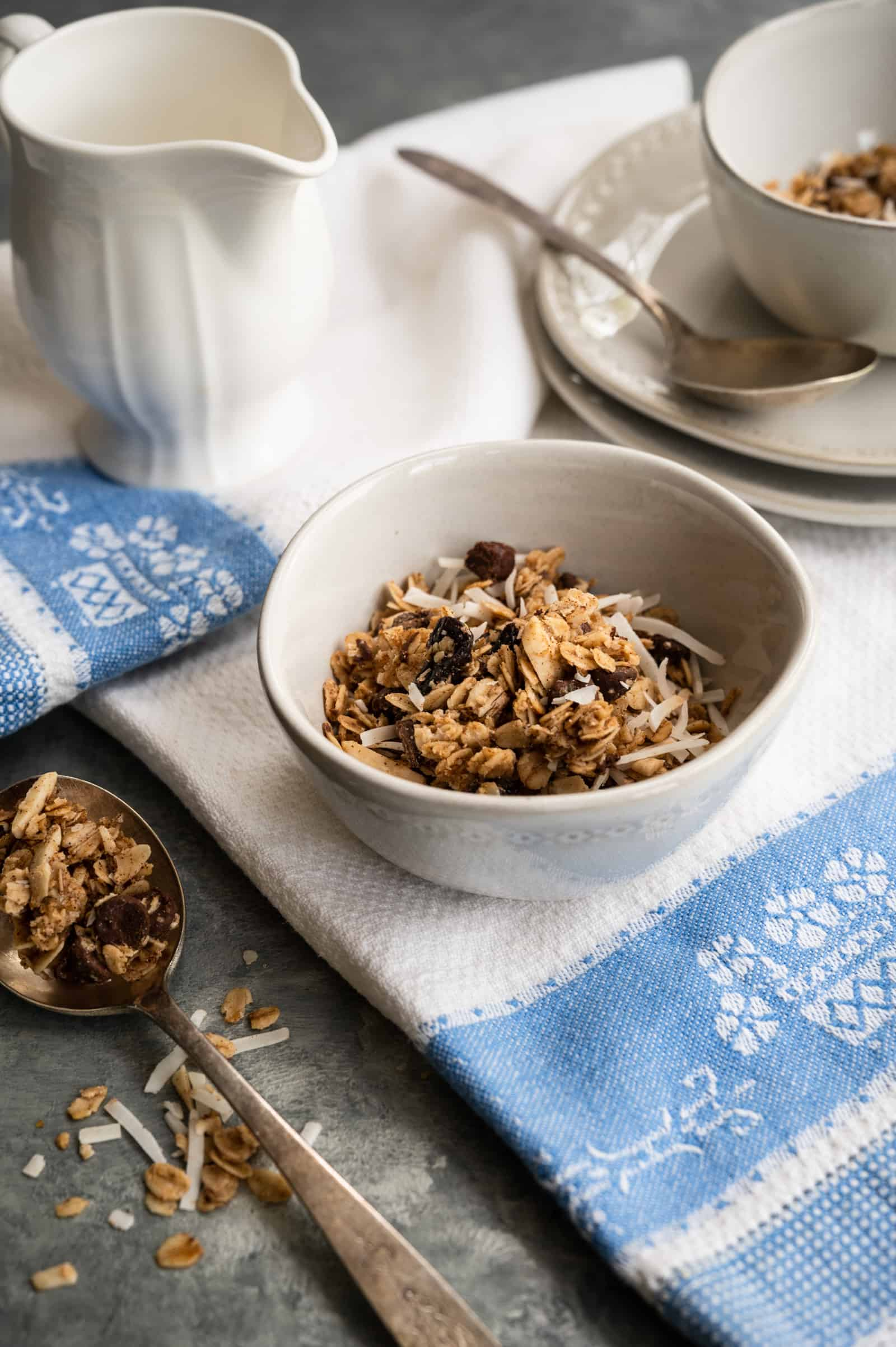 bowls of granola with a spoon on a gray background and blue and white dish towel