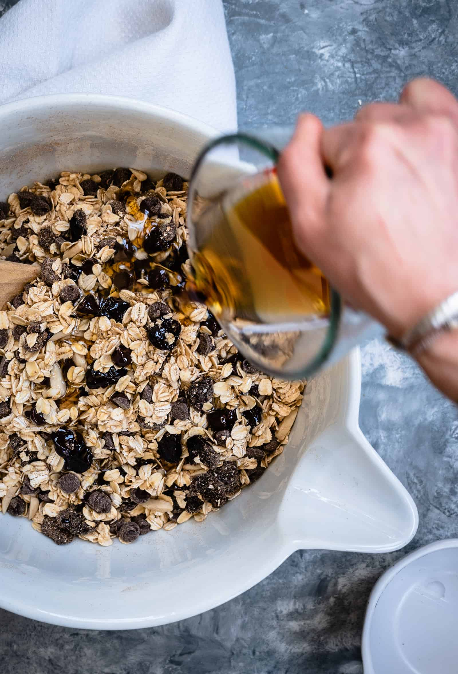 white mixing bowl with granola ingredients and hand pouring maple syrup into bowl