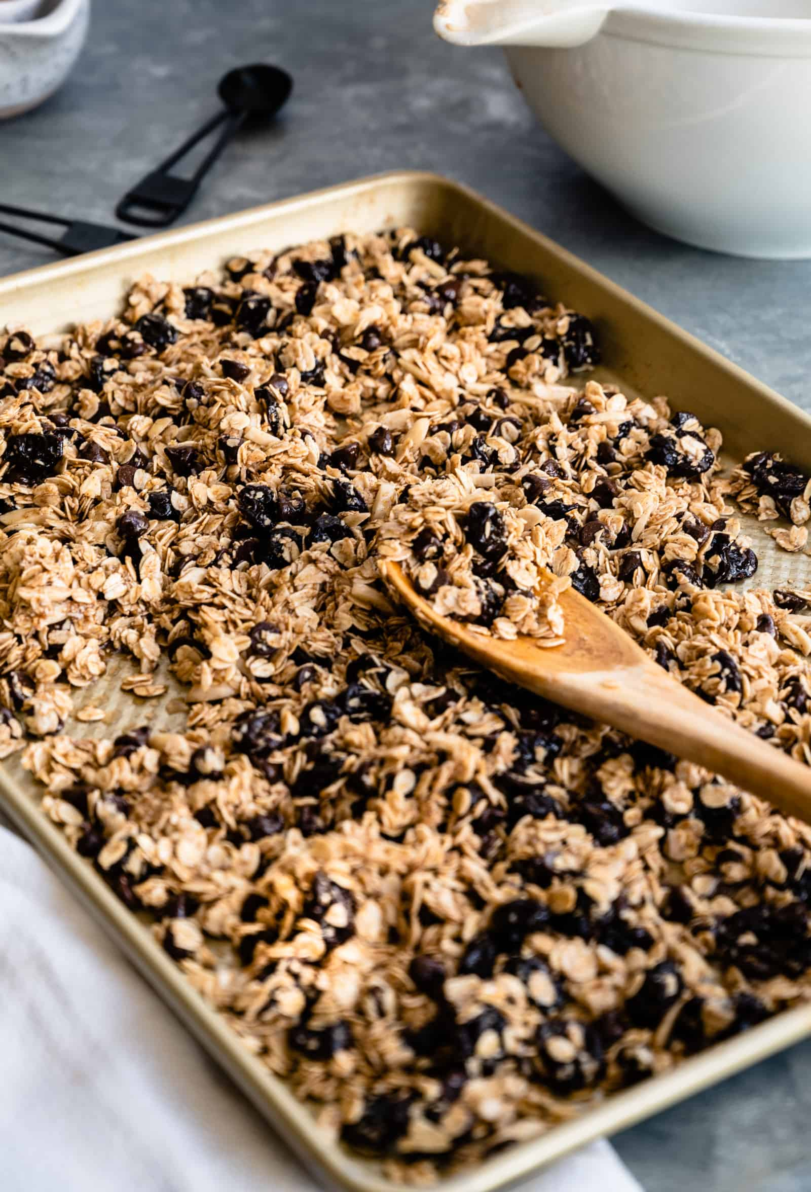 sheet pan of granola with a wooden spoon
