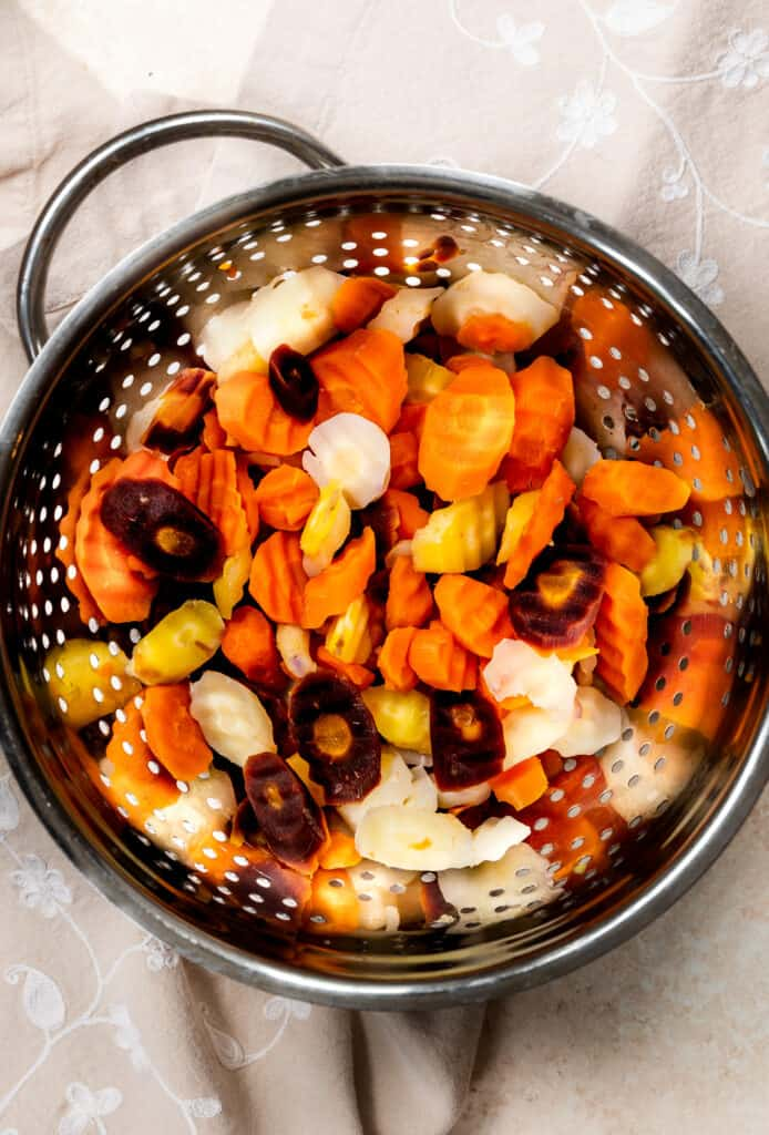 cooked rainbow carrots in a silver colander on a cream background