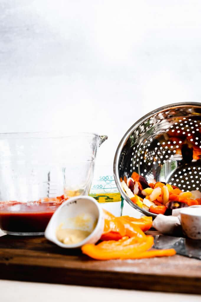 salad dressing ingredients and cooked carrots in a colander