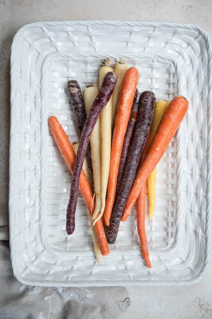 white basket tray of rainbow carrots on a cream background