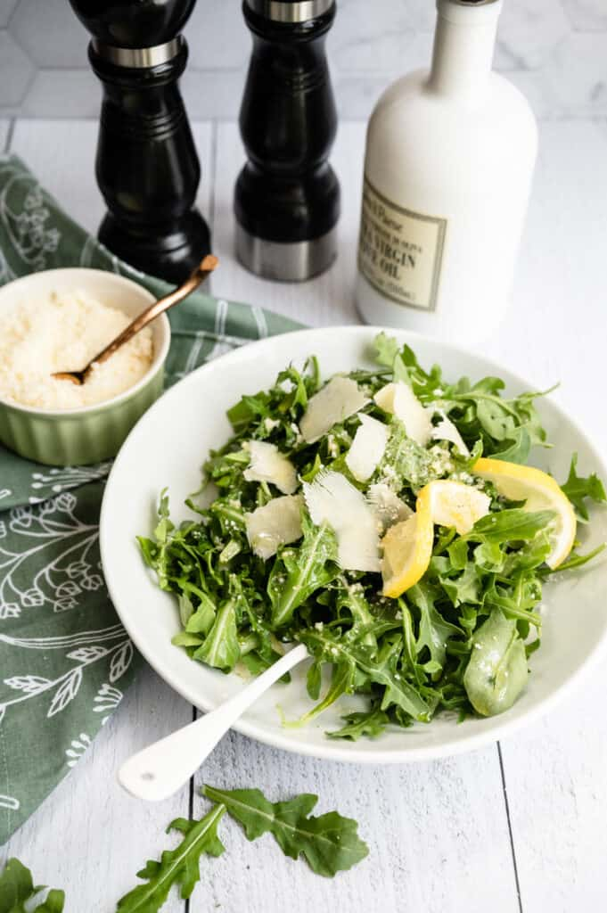 white bowl of arugula, parmesan and lemon slices on a green and white floral napkin and white wooden background with bowl of parmesan,white olive oil bottle and salt and pepper shakers
