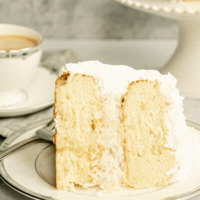 piece of coconut cake on a plate with a cup of coffee