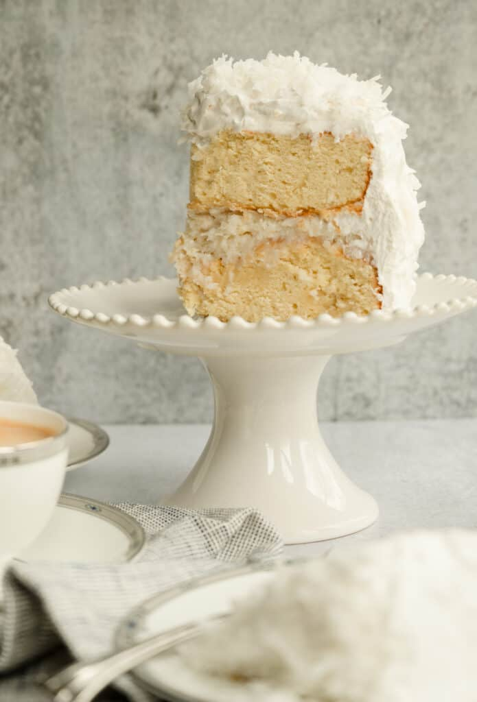 big piece of coconut cake standing up on a small white cake plate with coffee in the foreground