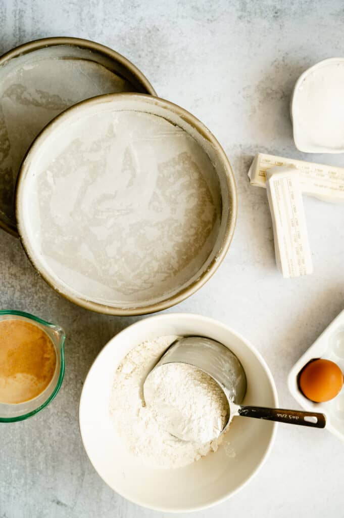 overhead shot of coconut cake ingredients in a white bowl and parchment paper pans