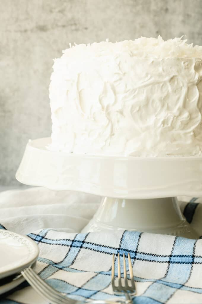 finished coconut cake on a white cake platter with a blue and white striped towel