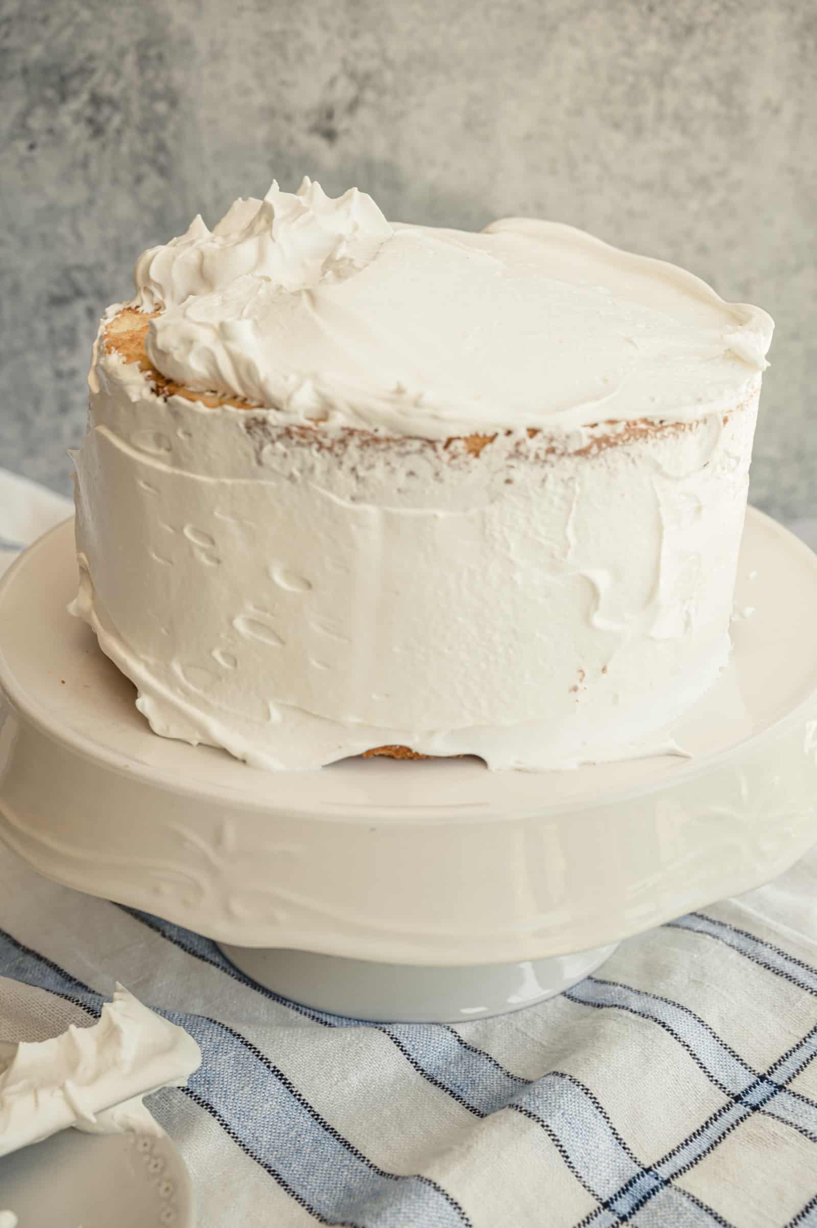 coconut cake being frosted with marshmallow meringue frosting