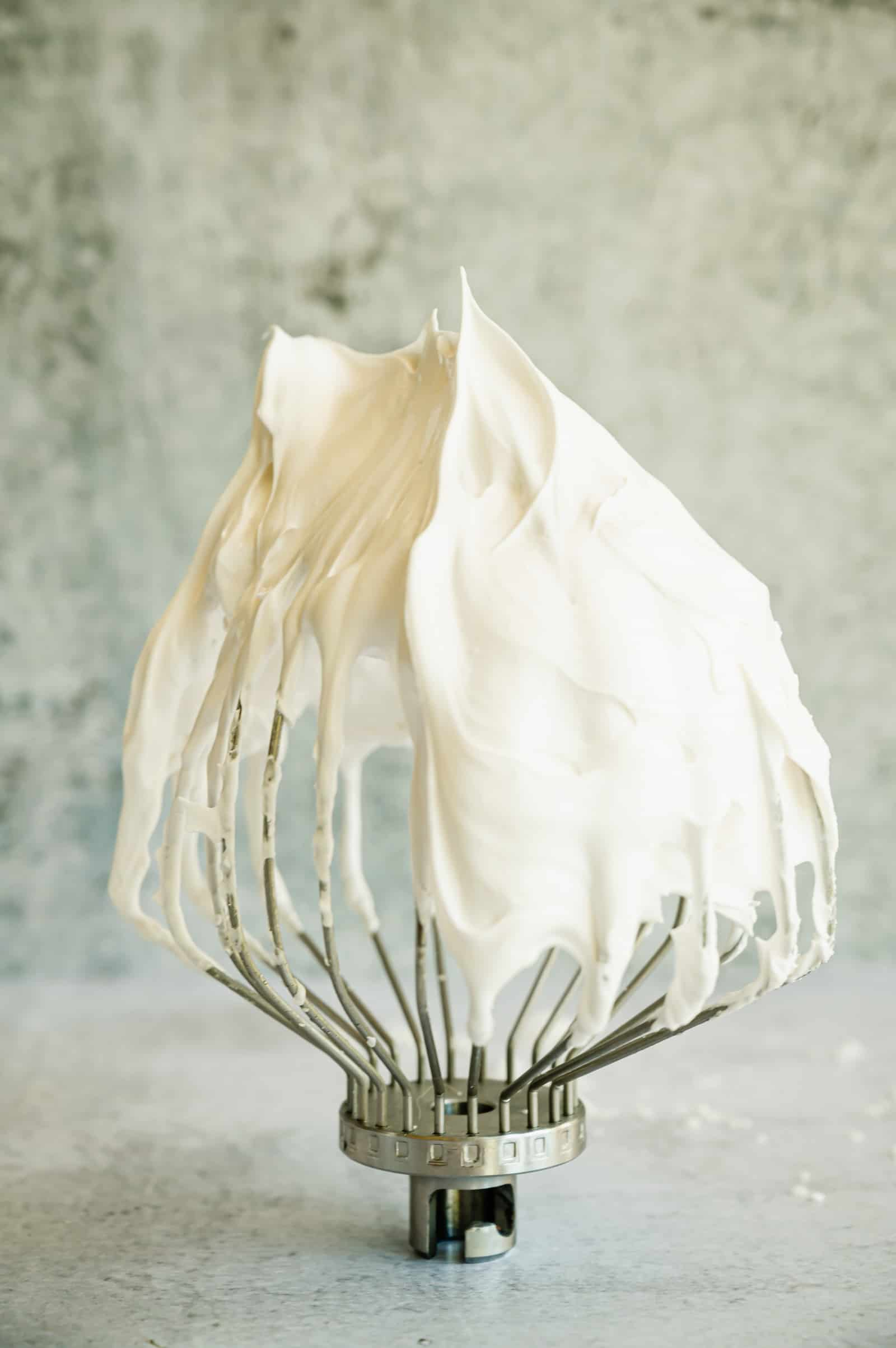 closeup of whisk with marshmallow meringue frosting