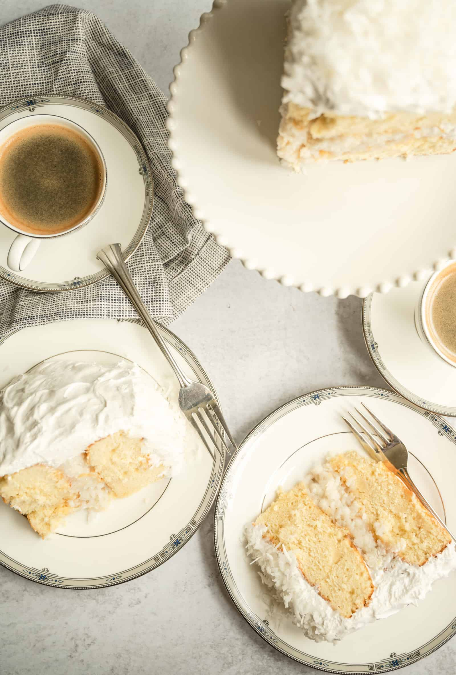 overhead shot of two pieces of coconut cake with coffee