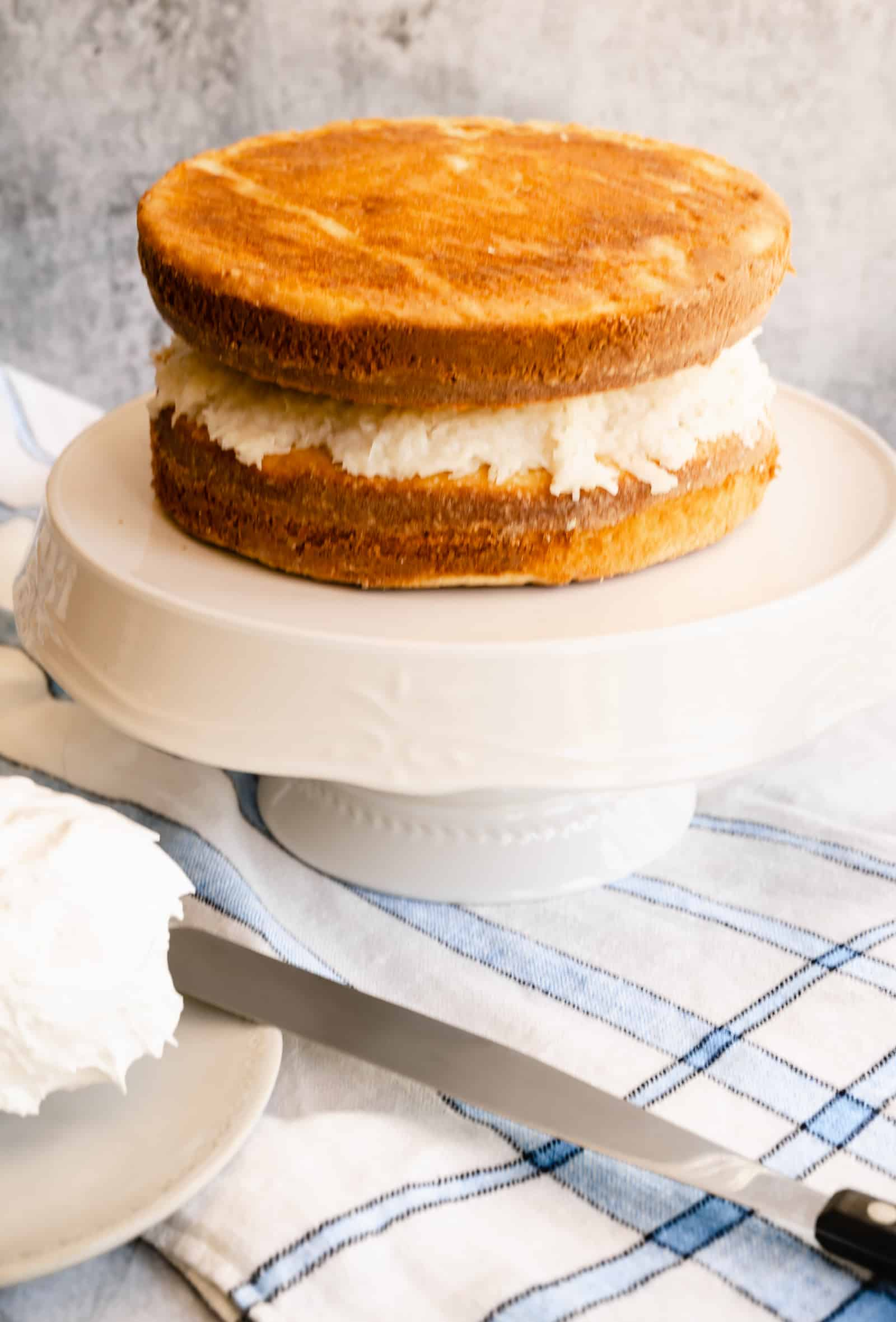 vanilla butter cake layers stacked with coconut filling on a white cake platter sitting on blue and white striped towel with a frosting spatula