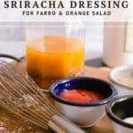 mason jar of salad dressing with two small bowls of sriracha, salt, and a whisk on a wooden cutting board