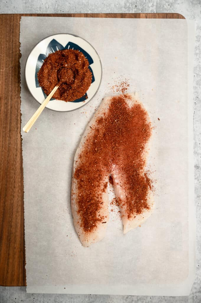 piece of tilapia seasoned with spices on a parchment covered cutting board with a bowl of spice mix next to it
