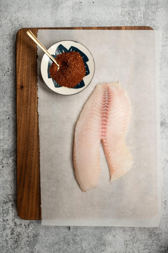 piece of tilapia on a parchment covered cutting board with a bowl of spice mix next to it