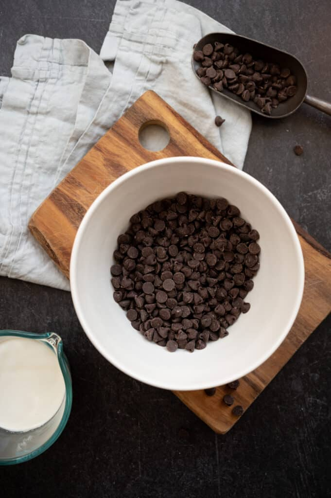 white bowl of chocolate chips on wooden cutting board with measuring cup of whipping cream