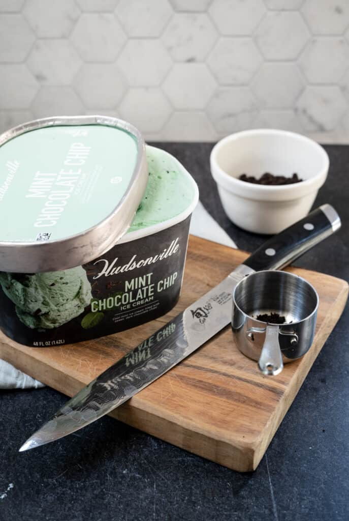 a container of mint chocolate chip ice cream, a knife, measuring cup and white bowl with cookie crumbs all on a wooden cutting board