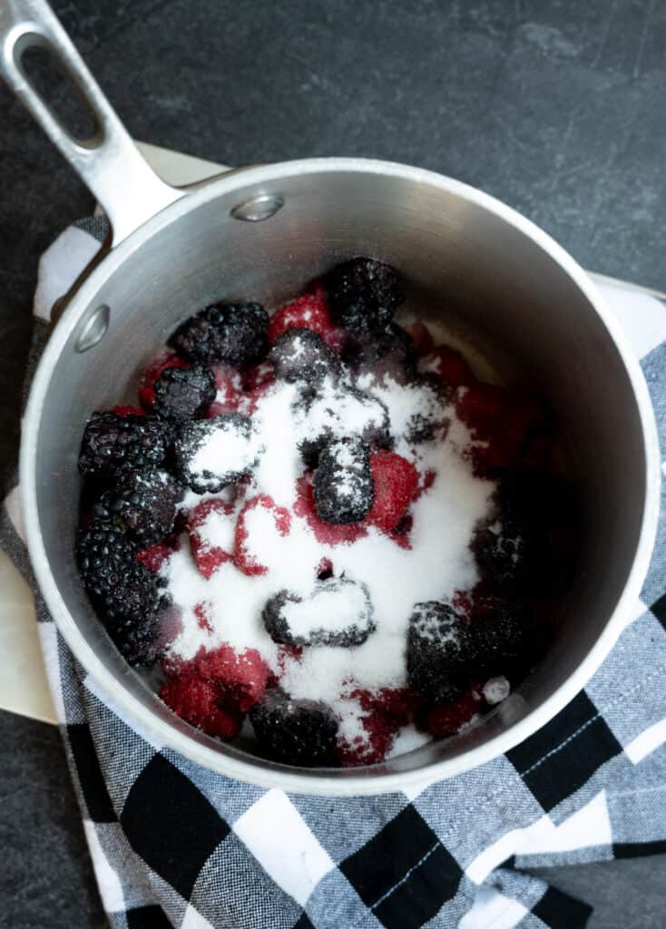 saucepan of blackberries, raspberries and sugar on a black and white checked napkin