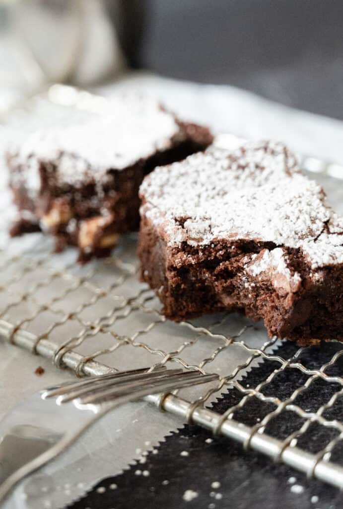 closeup of two brownies on a cooling rack with a fork and a bite taken out