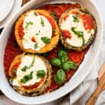 white pan of baked breaded eggplant with tomato sauce, cheese and basil