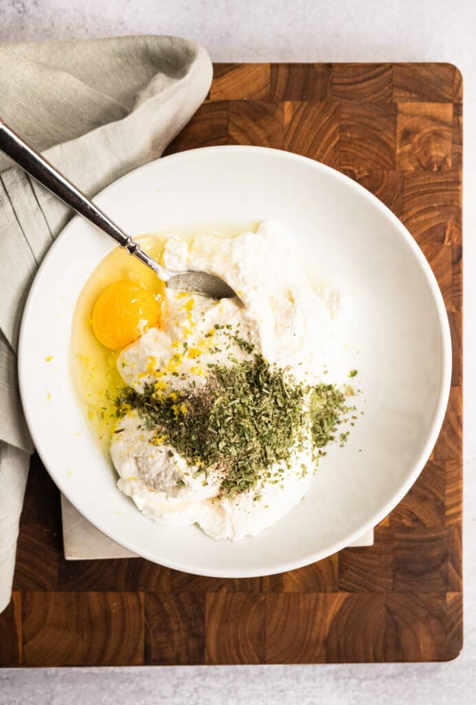 white bowl of ricotta, parmesan, parsley, and a raw egg with a fork on a wooden cutting board