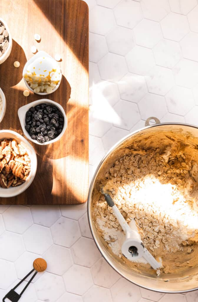 mixing bowl of cookie dough with assorted bowls and cups with chocolate chips, dried fruit and nuts on a marble background