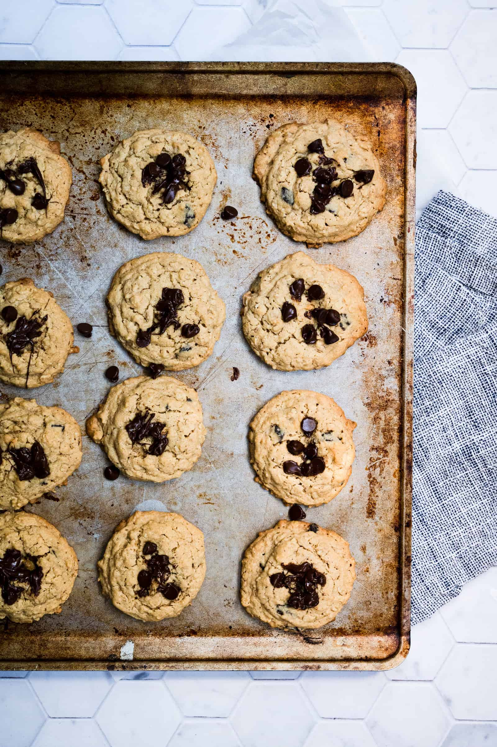 baking sheet of baked oatmeal chocolate chip cookies on a blue and white napkin and marble background