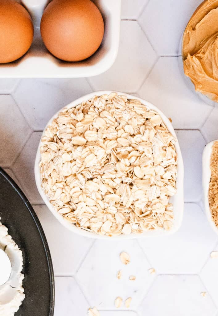 cup of oatmeal with eggs, peanut butter and flour on a marble background