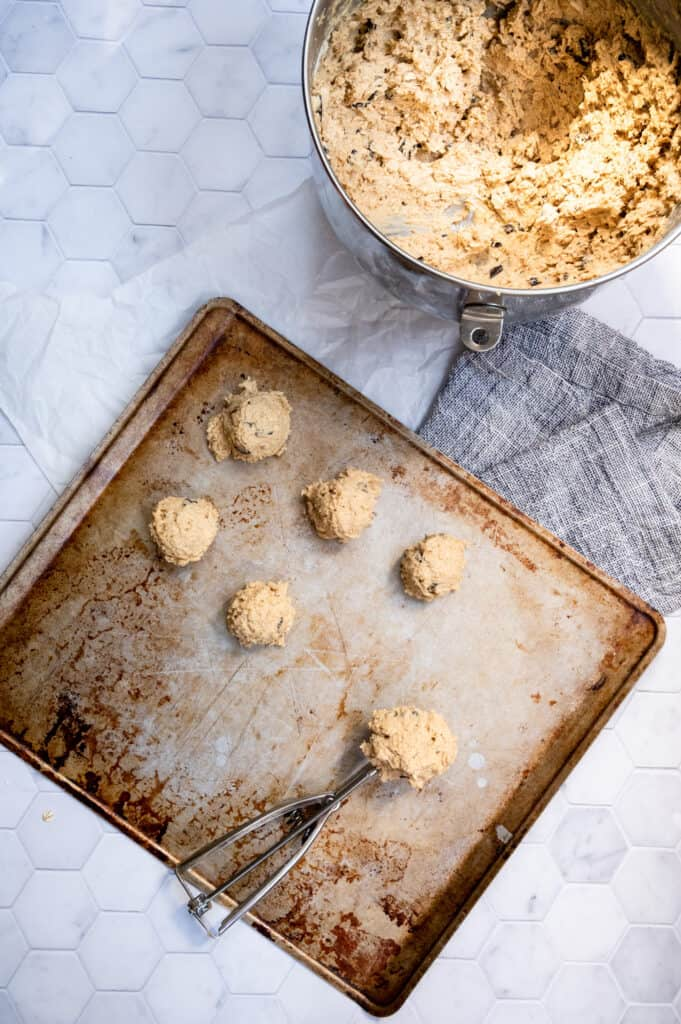 cookie dough being scooped onto a baking sheet with a mixing bowl of dough and a blue and white napkin