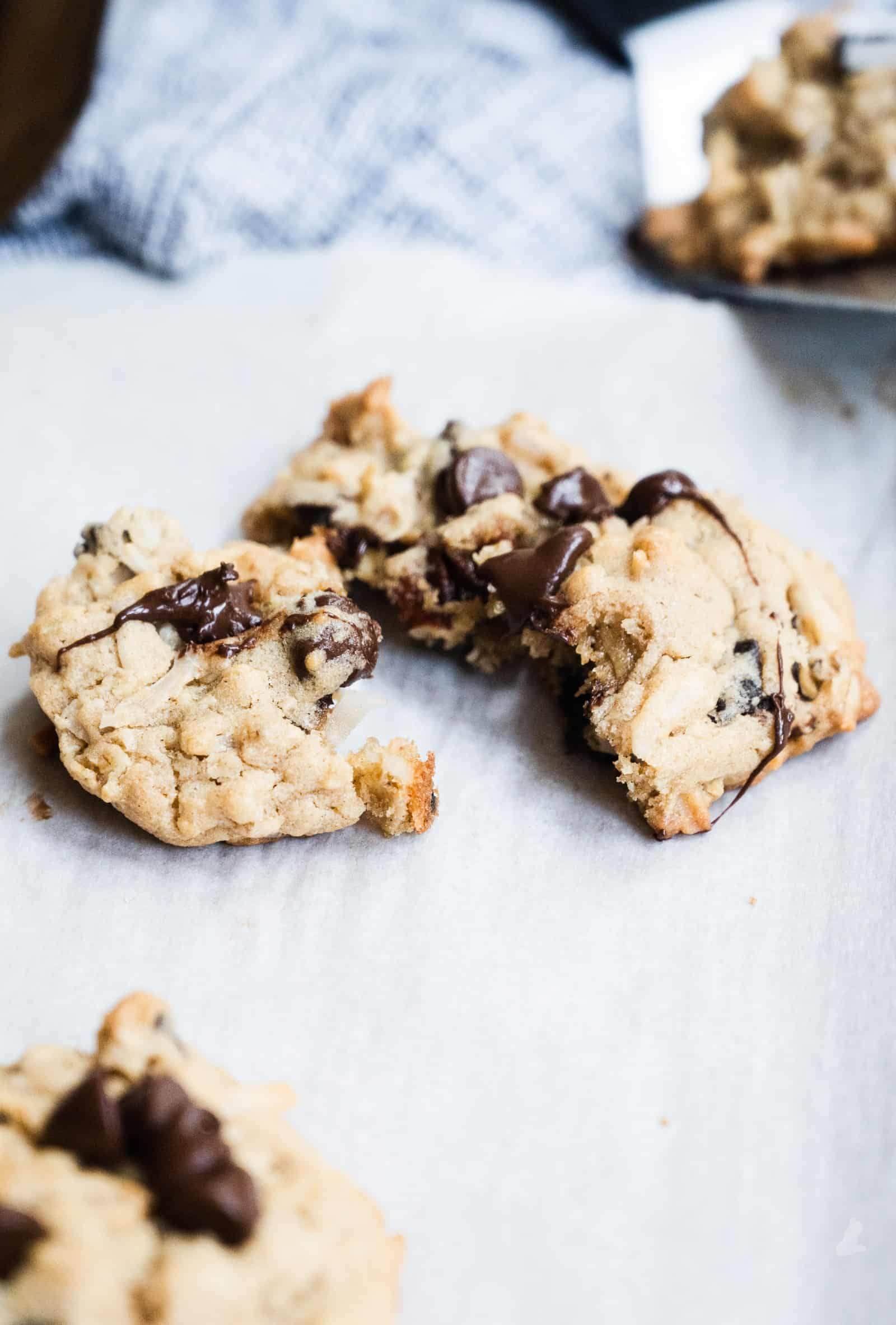 closeup of broken apart oatmeal chocolate chip cookie on parchment paper