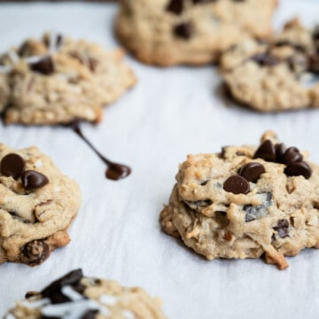 closeup of oatmeal chocolate chip cookies with a smear of melted chocolate on parchment paper