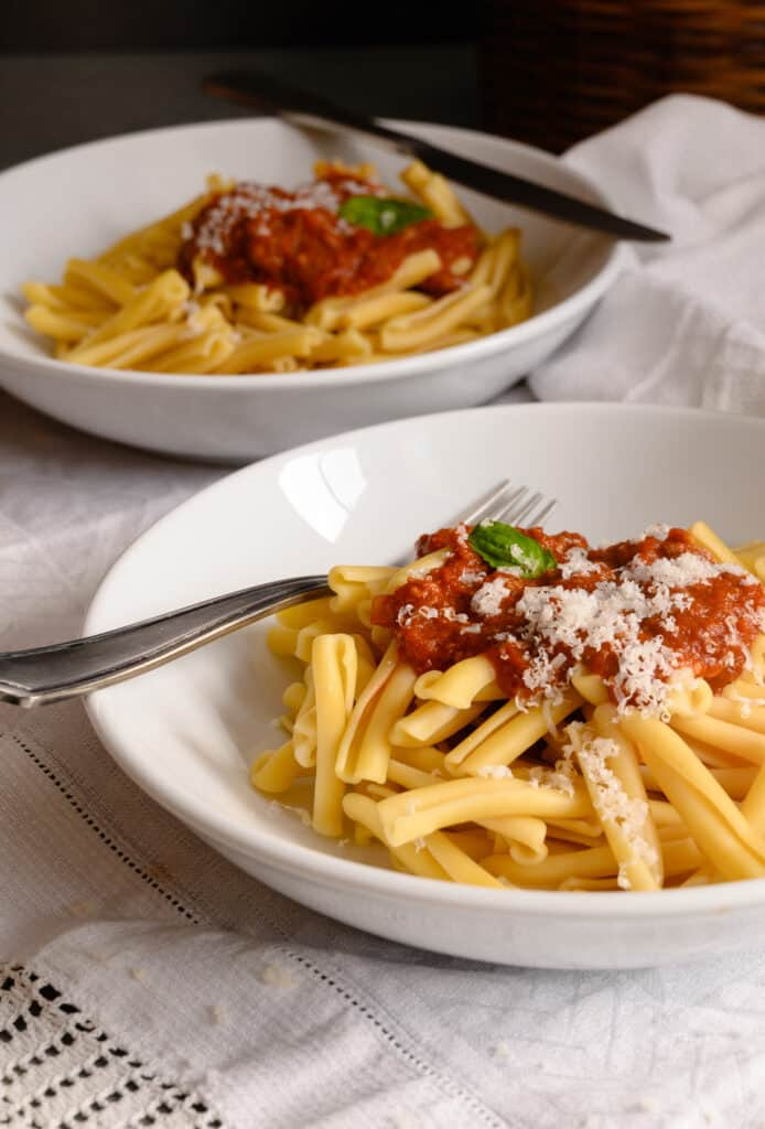 two bowls of pasta with tomato sauce and cheese