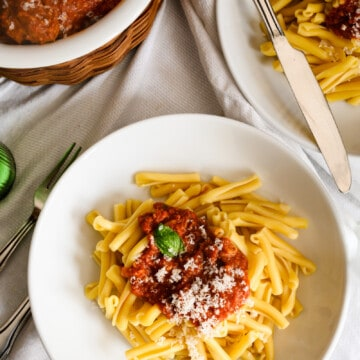 two bowls of pasta with tomato sauce and bowl of meatballs and cheese