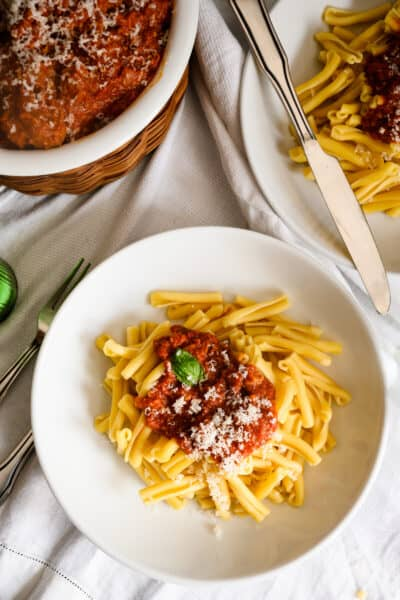 two bowls of pasta with tomato sauce and bowl of meatballs and cheese.