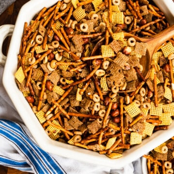 white bowl of chex mix and a wooden spoon with a blue dish towel on a wooden board.
