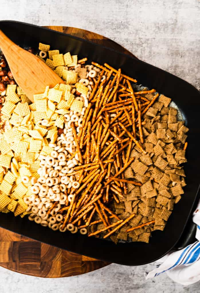 skillet of chex mix ingredients on a wooden board and blue and white towel