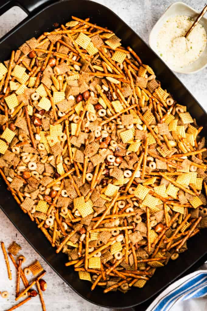 skillet of chex mix ingredients with a bowl of garlic salt