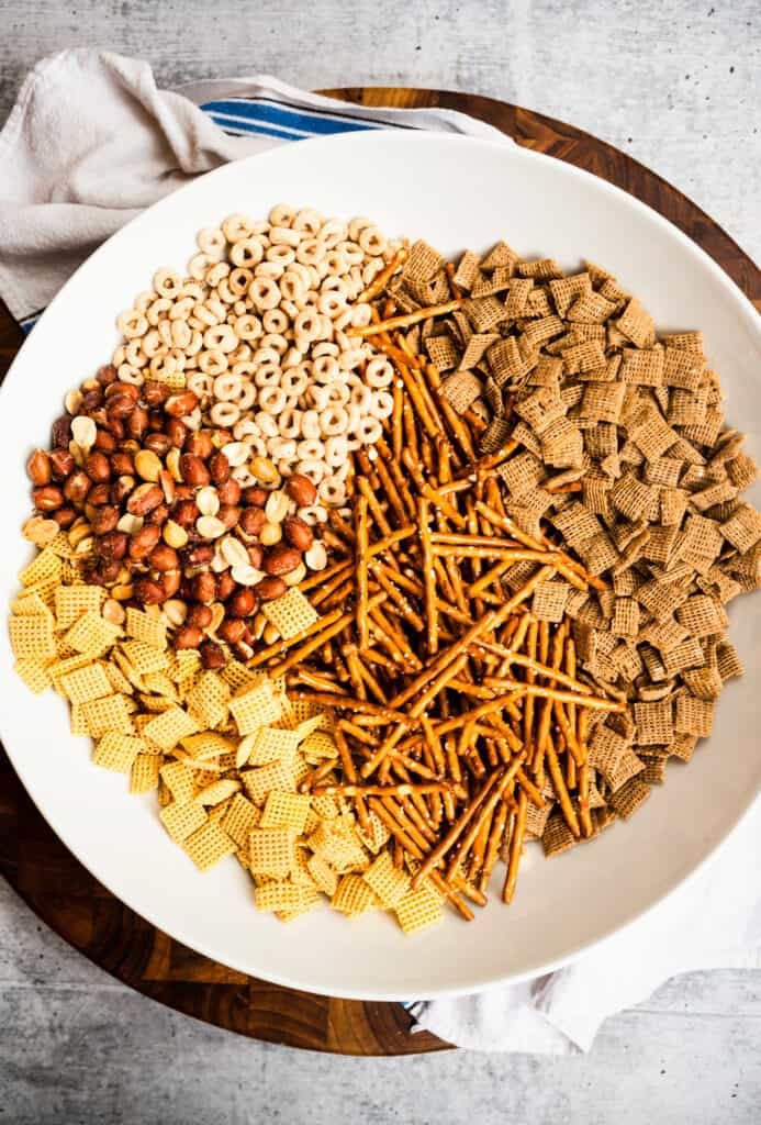 white bowl with cheerios, chex cereal, pretzels, peanuts on round board