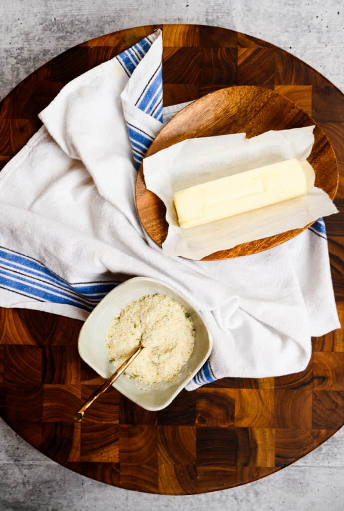 round board with blue and white towel and stick of butter and bowl of garlic salt