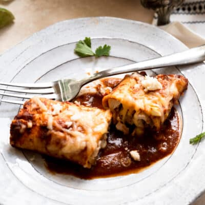 white plate of cut open enchilada and a fork