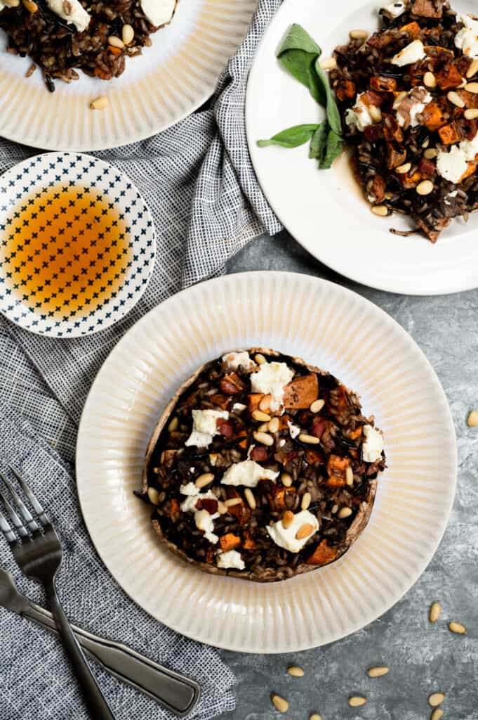 stuffed portobello mushrooms on a white dishes with little bowl of sherry honey