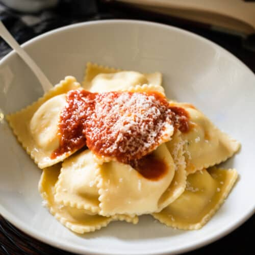 a white bowl with ravioli and tomato sauce and a white fork