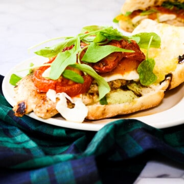 a white plate with a grilled chicken sandwich on a blue and green plaid napkin.