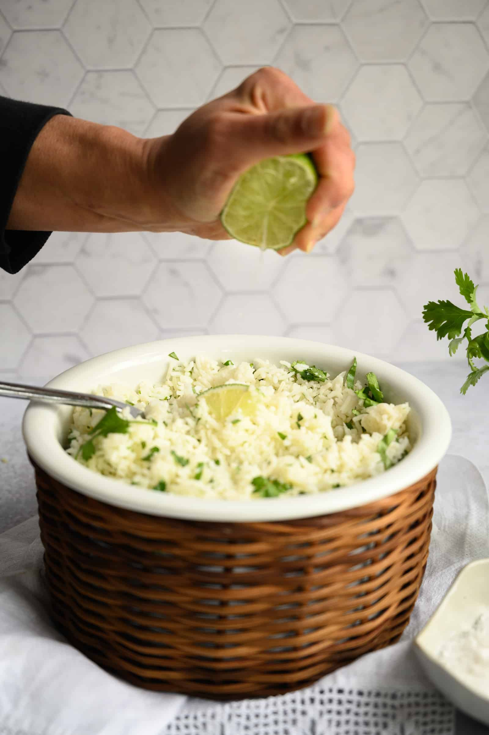 hand squeezing fresh lime over a white bowl of rice with cilantro